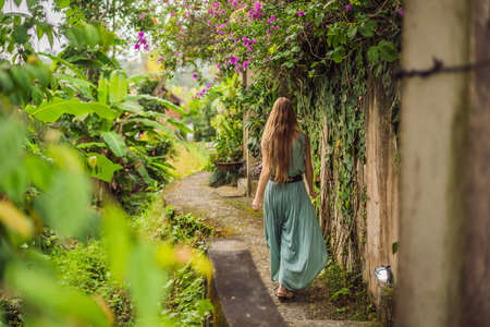 Young woman tourist in Bali walks along the narrow cozy streets of Ubud. Bali is a popular tourist destination. Travel to Bali concept.