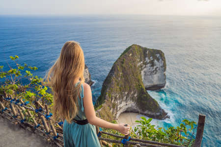 Family vacation lifestyle. Happy woman stand at viewpoint. Look at beautiful beach under high cliff. Travel destination in Bali. Popular place to visit on Nusa Penida island.