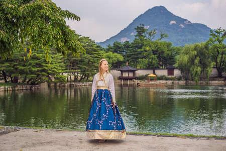 Young caucasian female tourist in hanbok national korean dress at Korean palace. Travel to Korea concept. National Korean clothing. Entertainment for tourists - trying on national Korean clothing Stock Photo