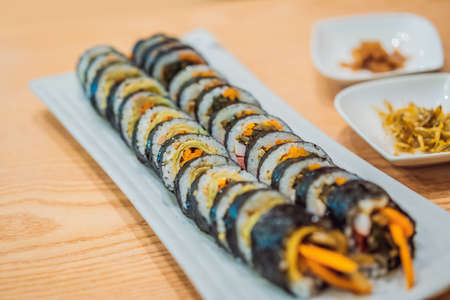 Gimbap or Kimbap is a Korean dish made from steamed white rice bap and various other ingredients, rolled in gim sheets of dried laver seaweed and served in bite-size slices 스톡 콘텐츠