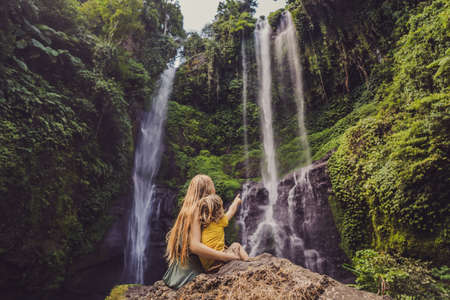 Mather and son at the Sekumpul waterfalls in jungles on Bali island, Indonesia. Bali Travel Concept