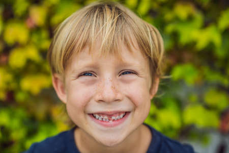 Little smiling child boy hand pointing his first tooth fall out