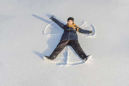 Woman warmly clothed in a cold winter forest makes snow angel figure at park.