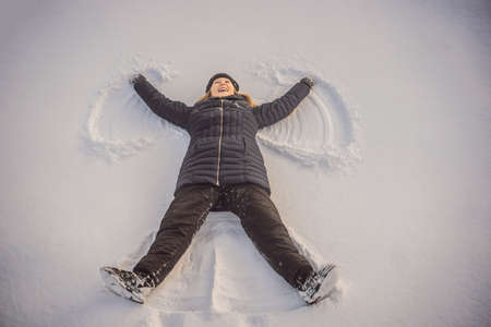 Woman warmly clothed in a cold winter forest makes snow angel figure at park. Reklamní fotografie