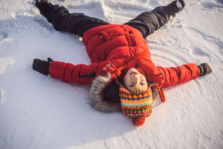 A child, a boy, lies on the snow