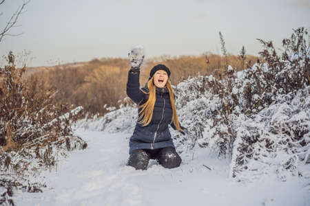 Girl throwing snowball at camera smiling happy having fun outdoors on snowing winter day playing in snow.
