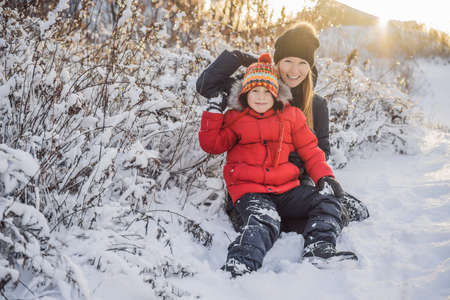 Mother and son throwing snowball at camera smiling happy having fun outdoors on snowing winter day playing in snow.
