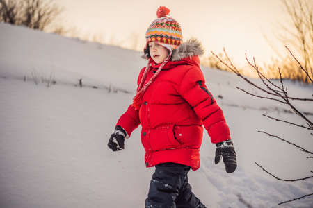 Cute boy in red winter clothes runs fun in the snow