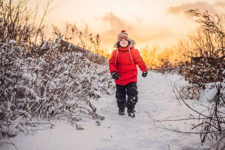 Cute boy in red winter clothes runs fun in the snow.