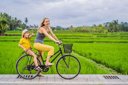 Mother and son ride a bicycle on a rice field in Ubud, Bali. Travel to Bali with kids concept