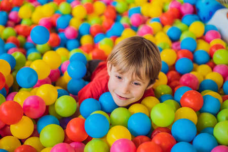 Glücklicher kleiner Junge, der an der hohen Ansicht des bunten Plastikballspielplatzes spielt Entzückendes Kind, das drinnen Spaß hat