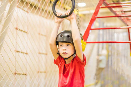 Portrait of 6 years old boy wearing helmet and climbing. Child in abstacle course in adventure playground