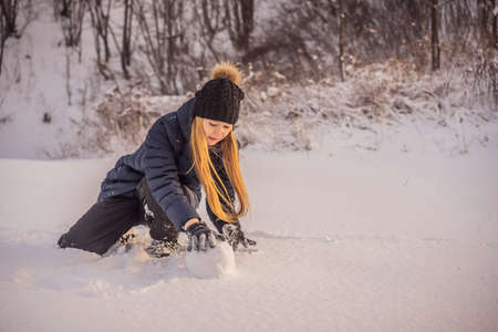 Young woman rolling giant snowball to make snowman
