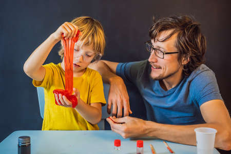 Father and son conduct chemical experiments at home. Home made slime. Family plays with a slime