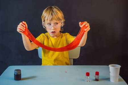 Boy playing hand made toy called slime. Child play with slime. Kid squeeze and stretching slime