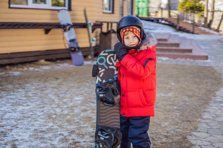 Little cute boy is ready for snowboarding. Activities for children in winter. Childrens winter sport. Lifestyle