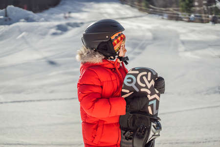 Little cute boy is ready for snowboarding. Activities for children in winter. Children's winter sport. Lifestyle.