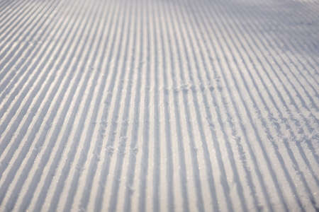 perfectly groomed empty ski run on a sunny winter day.