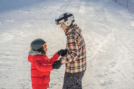 Mother teaches son snowboarding. Activities for children in winter. Children's winter sport. Lifestyle. 版權商用圖片