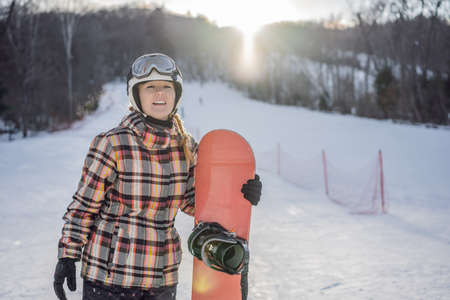 Woman snowboarder on a sunny winter day at a ski resort