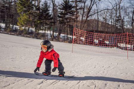 Little cute boy snowboarding.