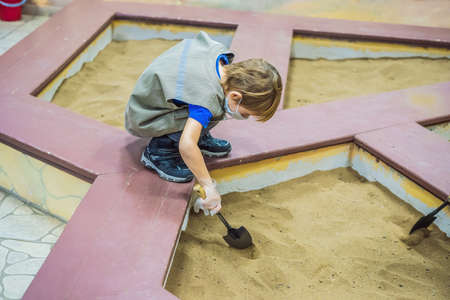 Happy boy using shovel finding hidden artifact under the ground Stock Photo