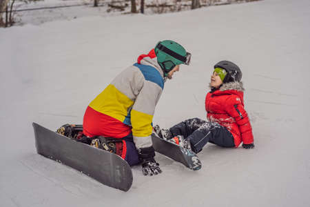 Snowboard instructor teaches a boy to snowboarding.
