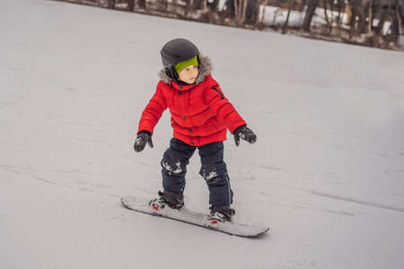 Little cute boy snowboarding. 版權商用圖片