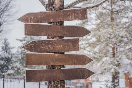 Wooden direction sign with snow on it and with snowfall on background. Imagens