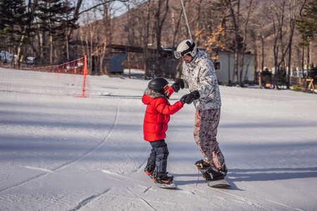 Dad teaches son snowboarding. Activities for children in winter. Childrens winter sport. Lifestyle Stockfoto
