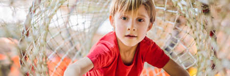 Boy crawls on a net in an obstacle course BANNER, LONG FORMAT