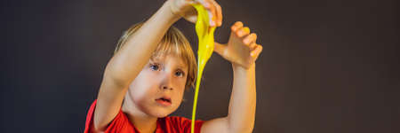 Boy playing hand made toy called slime. Child play with slime. Kid squeeze and stretching slime BANNER, LONG FORMAT