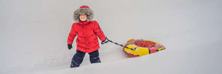 Child having fun on snow tube. Boy is riding a tubing. Winter fun for children BANNER, LONG FORMAT