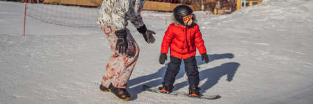 Dad teaches son snowboarding. Activities for children in winter. Childrens winter sport. Lifestyle BANNER, LONG FORMAT Stockfoto