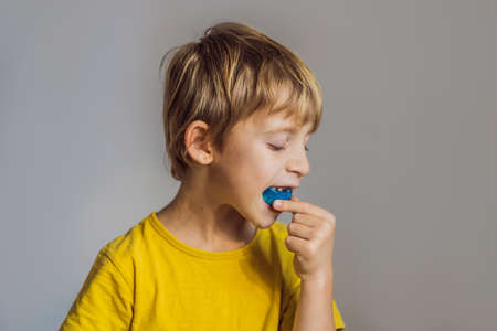 Six-year old boy shows myofunctional trainer. Helps equalize the growing teeth and correct bite, develop mouth breathing habit. Corrects the position of the tongue Standard-Bild