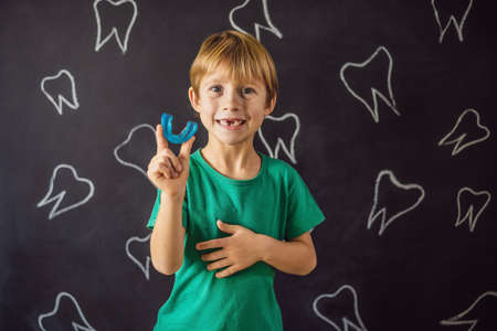 Six-year old boy shows myofunctional trainer. Helps equalize the growing teeth and correct bite, develop mouth breathing habit. Corrects the position of the tongue Banco de Imagens