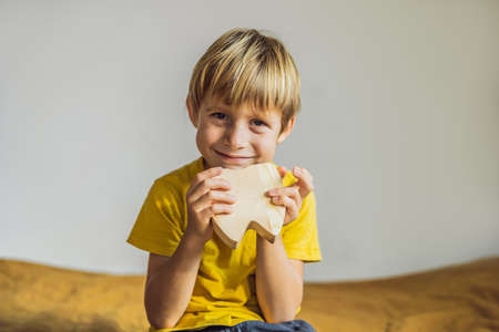A boy, 6 years old, holds a box for milk teeth. Change of teeth