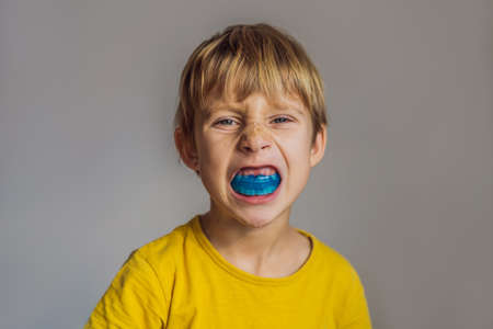 Six-year old boy shows myofunctional trainer. Helps equalize the growing teeth and correct bite, develop mouth breathing habit. Corrects the position of the tongue
