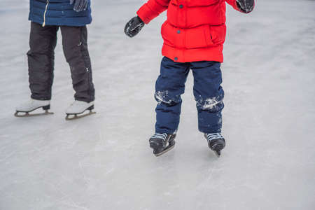 young mother teaching her little son ice skating at outdoor skating rink. Family enjoy winter on ice-rink outdoors.