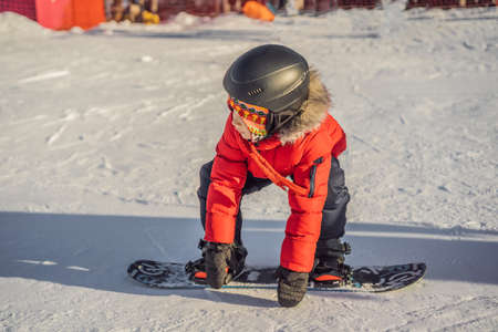 Little cute boy snowboarding. Activities for children in winter. Children's winter sport. Lifestyle. 版權商用圖片