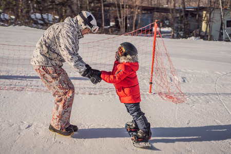 Dad teaches son snowboarding. Activities for children in winter. Childrens winter sport. Lifestyle 免版税图像