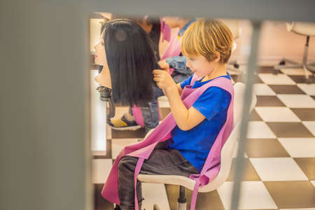 boy hairdresser, day of choice of profession, play at the hairdresser in the childrens beauty salon, hairstylist, hairdressing, barber job.