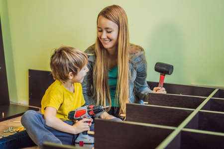 Mother and son assembling furniture. Boy helping his mom at home. Happy Family concept Banque d'images