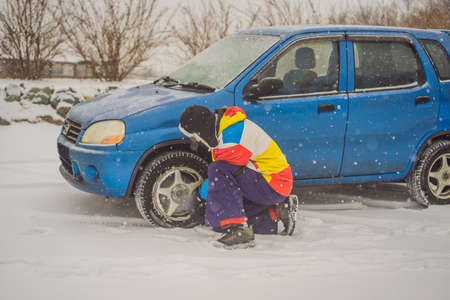 Winter accident on the road. A man changes a wheel during a snowfall. Winter problems.