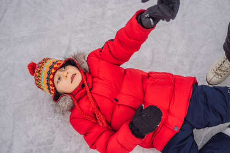 boy ice skating fell down on the ice rink