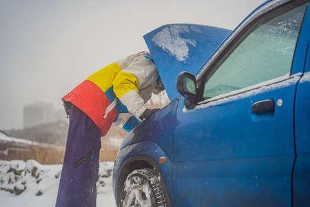 upset young men looking under the hood broken car on winter road.