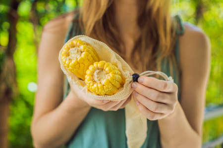 Corn in a reusable bag in the hands of a young woman. Zero waste concept
