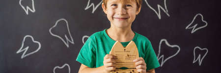 A boy, 6 years old, holds a box for milk teeth. Change of teeth BANNER, LONG FORMAT