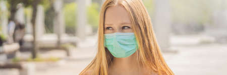 Blonde hair woman in protective surgical mask. Concept of spread of Chinese Coronavirus 2019-nCoV virus around world BANNER, LONG FORMAT Stockfoto