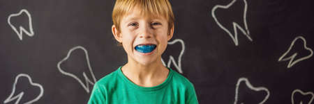 BANNER, LONG FORMAT Six-year old boy shows myofunctional trainer. Helps equalize the growing teeth and correct bite, develop mouth breathing habit. Corrects the position of the tongue Banco de Imagens